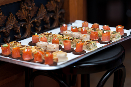 Appetizers on silver platter on wooden chair Фото со стока