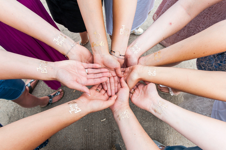 Group of woman holding hands with golden tattoo Фото со стока