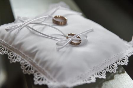 Golden wedding rings on white satin pillow with ribbon