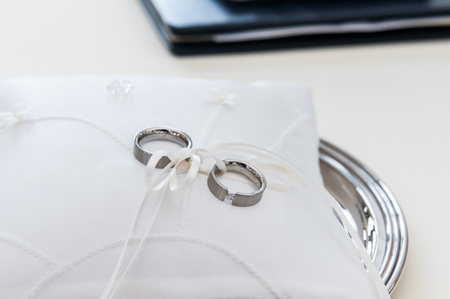 Silver weddings rings on white pillow