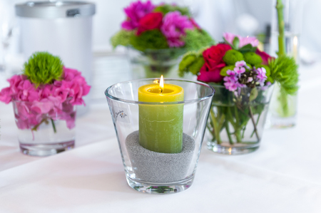 Candle in glass on white table Фото со стока