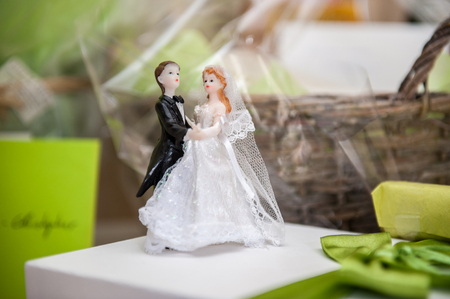 Bride and groom made of sugar on top of wedding cake Фото со стока