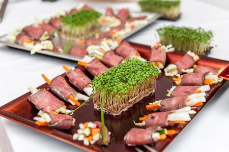 Roast beef appetizers on porcelain plate