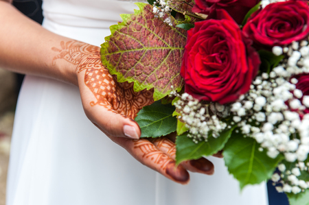 Henna on a bride`s hand with flower bouquet