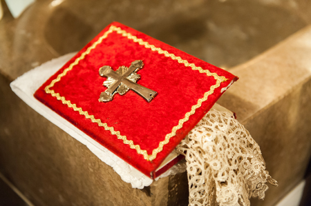 Red holly book with metal cross in church