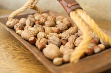 Walnuts and peanuts in a wooden bowl with handle Фото со стока