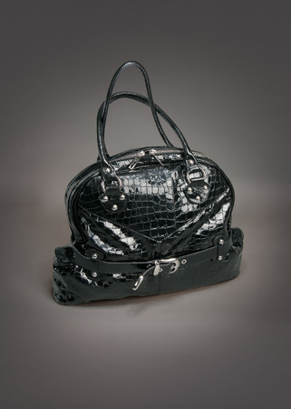 Black leather bag on gradient gray background