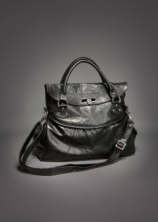 Black leather handbag on gradient gray background