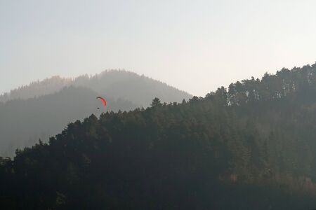Paraglider flying over mountains in summer day
