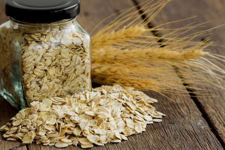Oat flakes on wood table and carry in glass jar. Healthy food. Stock Photo
