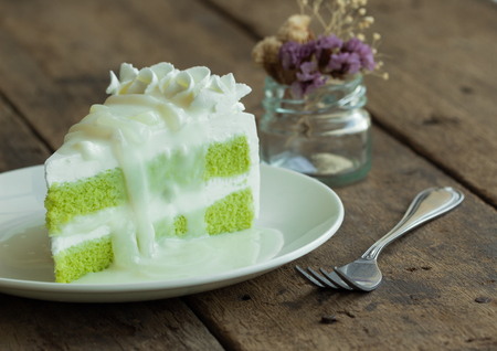 Pandan cake frosting by wipped cream topping with young toddy palm seed in coconut milk sauce on white plate put on wood table. Thai style dessert.