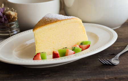 Homemade Japanese cheesecake. Absolutely delicious, fluffy,lite and soft. Serve with sparkling icing, fresh fruit such as kiwi and strawberry on white plate put on wood table for your relax time. Low fat bakery.