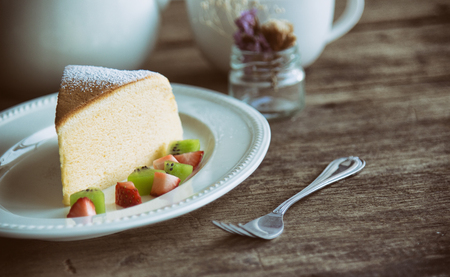 Homemade Japanese cheesecake. Absolutely delicious, fluffy,lite and soft. Serve with sparkling icing, fresh fruit such as kiwi and strawberry on white plate put on wood table for your relax time. Low fat bakery. Vintage style.
