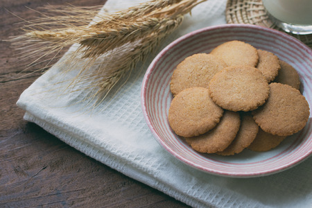 Homemade bakery:Thin biscuits or cookies baked from multi grains so delicious, crisp and crack snack. Biscuits cookies on rustic wood table serve with fresh milk. Golden brown cookies on lovely plate.