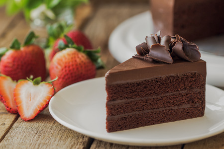 Eigengemaakte bakkerij: chocolade zachte toffeecake versierd met chocoladekrul. Driehoek segment stuk chocoladetaart op rustieke houten tafel voor café, vergadering, koffiepauze of tea time en verjaardagsfeestje.