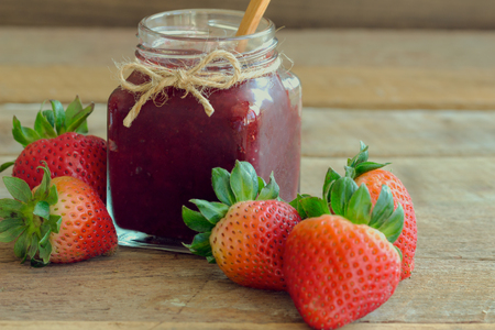 Homemade strawberry jam in bottle put on rustic wood table. Strawberry jam background with copy space for your design. Fresh strawberries and homemade jam on wood table in natural tone style concept.