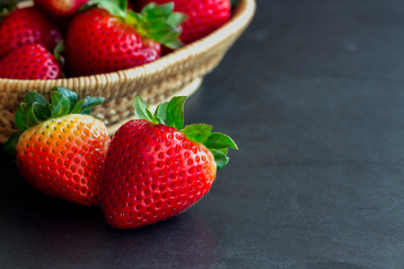 Fresh strawberries on granite background. Ripe strawberry in basket on granite table. Copy space background of strawberry for your design. Extremely exposure fruit  concept background or wallpaper.