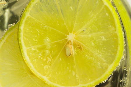 infused: Close up concept on piece of lemon or lime in lemonade for wallpaper or background. Half-circle of lemon or lime in sparkling water (soda) in natural tone. Water bubble and half-circle lemon or lime.