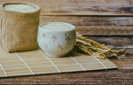 Japanese rice in gunny sack under sun light on bamboo sushi mat. Little lovely bowl filled with Japanese rice on rustic wood. Vintage warm tone style of Japanese rice of background and wallpaper.