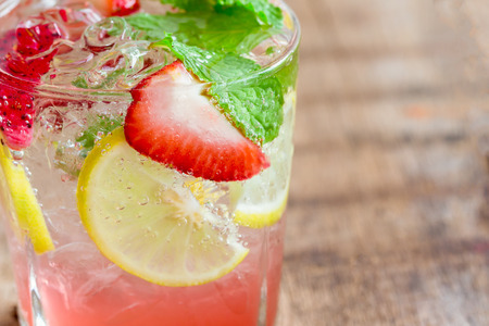 Strawberry lemon lime mojito in clear glass on rustic wood table. Homemade beverage strawberry soda ingredients with strawberry, lemon or lime and mint leaf. Homemade infused water close up concept.
