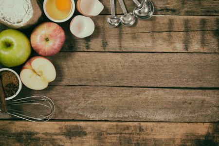 comprise: Bakery background comprise apples,wheat flour,egg and cinnamon on rustic wood table with copy space.Prepare ingredient for baking apple cake on wood table. Top view bakery background concept.