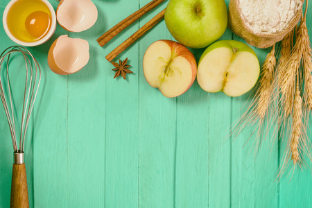 comprise: Bakery background comprise apples,wheat flour,egg and cinnamon on blue wood table with copy space.Prepare ingredient for baking apple cake on wood table. Top view bakery background concept. Stock Photo