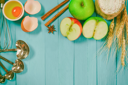 comprise: Bakery background comprise apples,wheat flour,egg, cinnamon notebook and pencil on blue wood table with copy space.Prepare ingredient for baking apple cake on wood table. Top view bakery background.