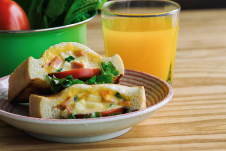 Pocket sandwich for breakfast or lunch. Homemade sandwich with hard boiled eggs and mayonnaise decorated by lettuce and tomato. Baked sandwich on lovely plate serve with orange juice on wood table.