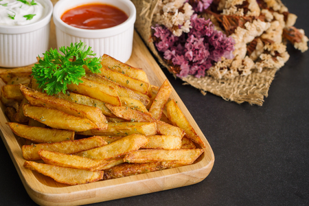 junk: Homemade french fries serve with ketchup and sour cream or mayonnaise. Golden brown crispy french fries sprinkle with salt and oregano on plate for snack or appetizer. French fries on granite table.