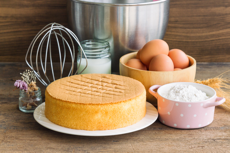 Homemade sponge cake on white plate.Soft and lite delicious sponge cake with ingredients: eggs flour milk on wood table. Homemade cake with ingredients in homemade bakery concept for bakery background