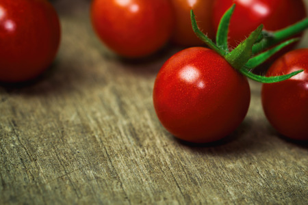 lycopene: Fresh cherry tomato on rustic wood table. Close up lovely cherry tomato for background or wallpaper. Prepare fresh cherry tomato for home cooking look so delicious. Macro concept with copy space.