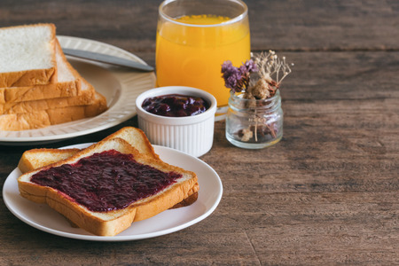 Toast bread with homemade strawberry jam served with orange juice. Homemade toast bread with strawberry jam on wood table for breakfast. Delicious toast bread with homemade jam ready to served.