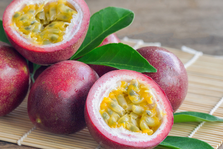 Close up fresh passion fruit stack on wood table in side view. Passion fruit is popular tropical fruits. Ripe passion fruit so juicy sweet and sour suitable make dessert for summer time.