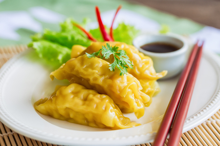 Homemade minced pork dumpling on white plate served with dipping soy sauce on wood table. Delicious dumpling or dim sum for breakfast or lunch or dinner. Dim sum or dumpling is popular Chinese food.