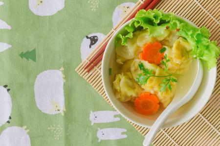 Selbst gemachte gehackte Schweinefleisch- und Garnelenwontonsuppe in der weißen Schüssel auf hölzerner Tabelle in der Draufsichtebenenlage Köstlicher Wonton in der klaren Suppe zum Frühstück oder Mittagessen oder Abendessen. Ponton oder Mehlkloß ist populäres chinesisches Lebensmittel. Standard-Bild - 87815030