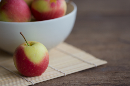 Fuji apple on bamboo mat put on rustic wood table and stack in white bowl with copy space. Delicious sweet and juicy fuji apple suitable for salad cooking or bakery. Fuji apple has origins in Japan.