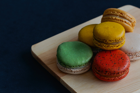 Colorful French macaron or Italian macaron stack on cutting board. Homemade delicious macaron on granite table with copy space for background or wallpaper. French dessert for served with tea or coffee Stock Photo