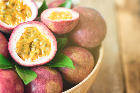 Close up fresh passion fruit in wood bowl on wood table in side view with copy space for background or wallpaper. Ripe passion fruit so delicious sweet and sour. Tropical fruit. Macro concept.