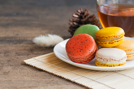 Homemade delicious colorful French or Italian macaron on white plate served with tea on wood table with copy space for background or wallpaper. Macaron is popular dessert for served with tea or coffee Stock Photo
