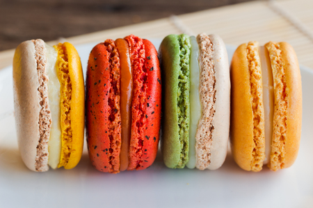 Close up homemade delicious colorful French or Italian macaron stack on white plate in horizontal for background or wallpaper. Macarons is popular dessert for served with tea or coffee. Macro concept.