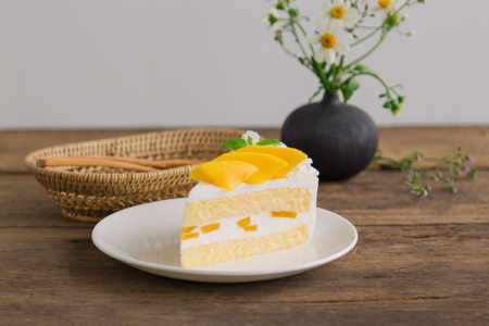 Homemade mango shortcake,sponge cake or soft cake on white plate decorate with ripe mango and mint on wood table. Mango is tropical fruits that make feel fresh on summer time. Sweet and sour dessert.