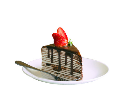 White isolated background with homemade chocolate crepe cake or mille crepe cover whipped cream topping dark chocolate sauce,mint,strawberry. Chocolate cake is delicious dessert.