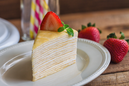 tarde de cafe: Delicious crepe cake on white plate decorated with mint served with strawberry sauce on wood table so soft sweet and sour. Homemade bakery concept of french dessert for birthday cake or cafe.