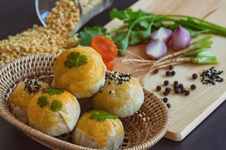 Chinese pastry or moon cake on wood basket with some ingredient on black granite table in top view, close up. Homemade bakery concept. Stock Photo
