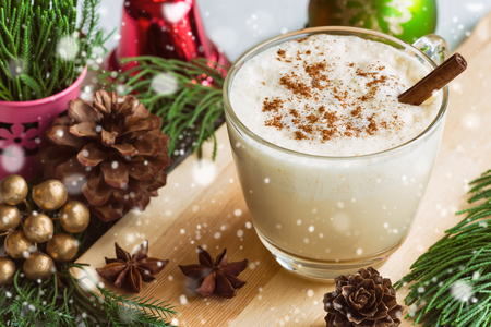 Eggnog, traditional drink for Christmas celebration party in glass topped with ground nutmeg and cinnamon stick, top view with copy space in Xmas theme decoration and snowfall effect background. Stock Photo