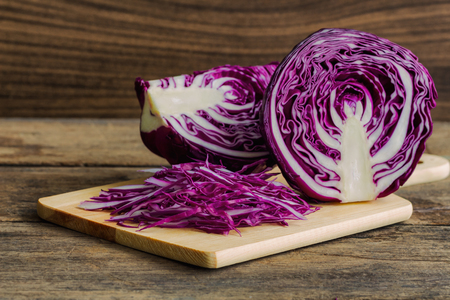 Chopped or sliced fresh purple cabbage on cutting board to shredded with knife kitchen on wood table with copy space. Prepare vegetable for cooking cabbage salad or coleslaw. Homemade food concept.