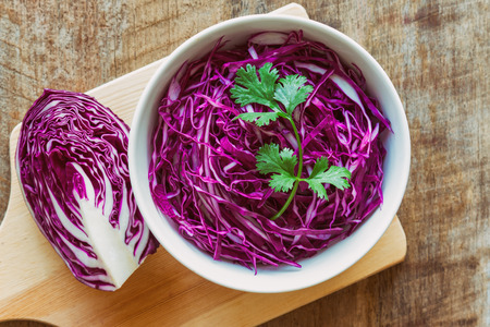 Cut or Sliced fresh purple cabbage in white bowl and decorate with coriander in top view flat lay on wood table. Prepare vegetable for cooking cabbage salad or coleslaw. Homemade food concept.