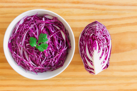Sliced fresh purple cabbage in white bowl to shredded and decorate with coriander in top view flat lay on wood table. Prepare vegetable for cooking cabbage salad or coleslaw. Homemade food concept.
