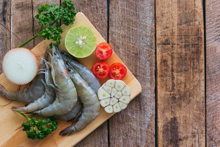 Fresh white shrimps on wood cutting board in top view flat lay with copy space. Prepared raw prawn and vegetable and herbs for cooking seafood menu on wooden table. Homemade delicious food concept.