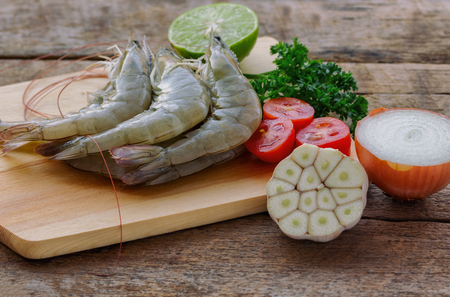Fresh white shrimps on wood cutting board in side view. Prepared raw prawn and vegetable and herbs for cooking seafood menu on wooden table. Homemade delicious food concept. Stock Photo
